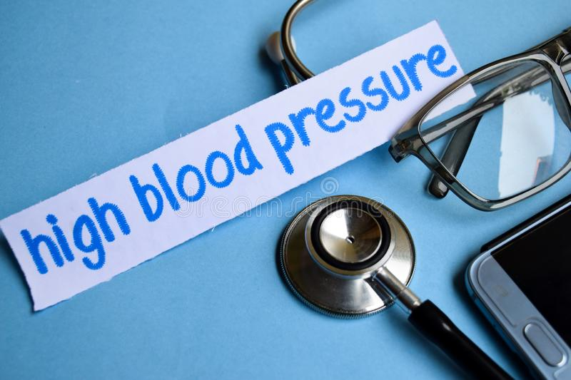 High blood pressure inscription with the view of stethoscope, eyeglasses and smartphone on the blue background. stock photos
