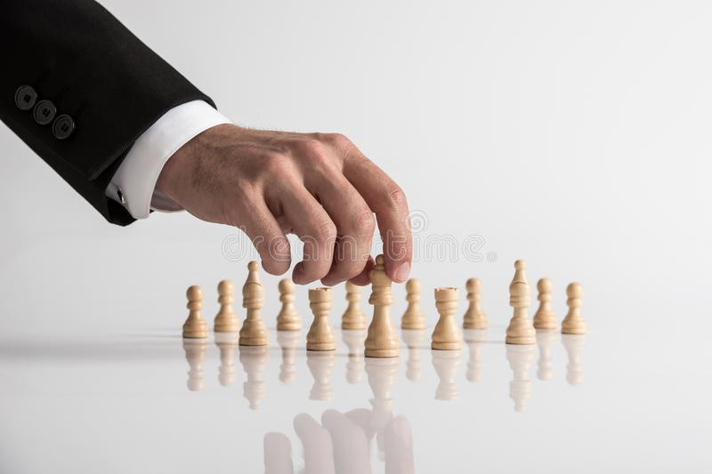 Conceptual image of human hand wearing business suit moving queen chess piece stock photos