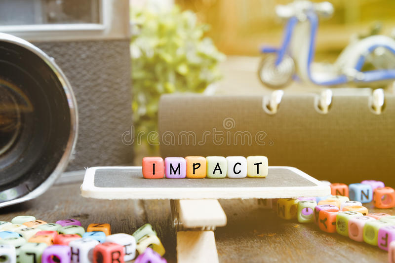 IMPACT word block on wooden signage over soft focus background stock photo