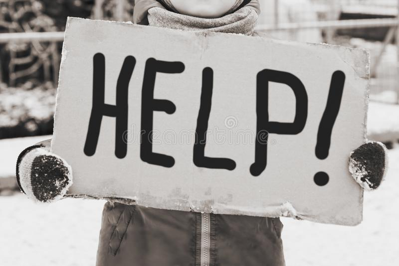 Conceptual image of a little child holding a handwritten HELP sign. Little kid standing and holding a handwritten HELP sign royalty free stock photo