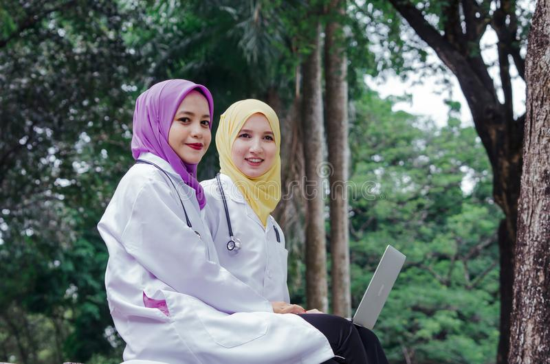 Medical muslimah doctors having a rest and discussion at park stock image