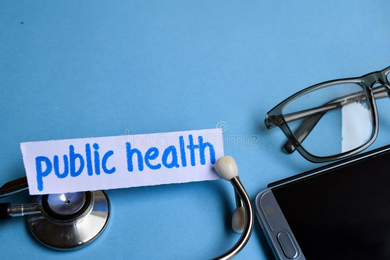 Public health inscription with the view of stethoscope, eyeglasses and smartphone on the blue background royalty free stock photos