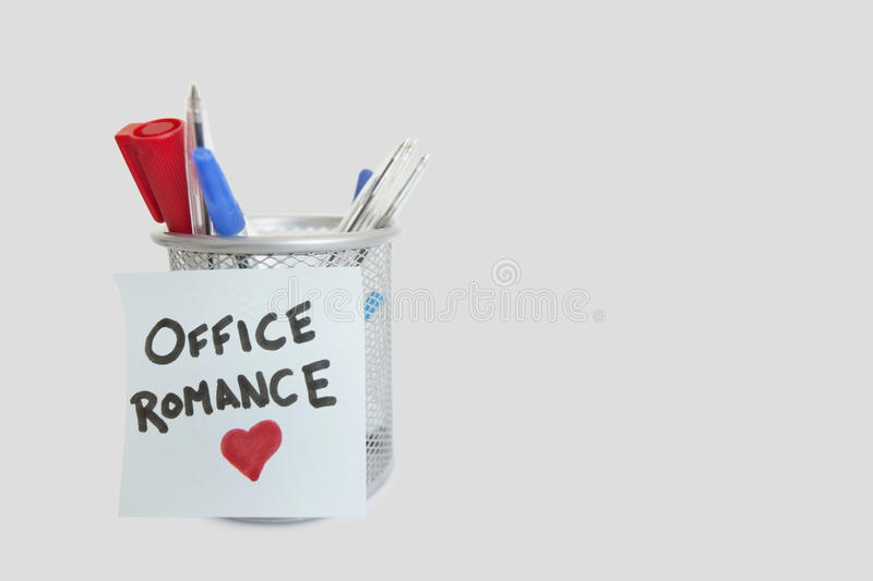Conceptual image of sticky notepaper with heart shape depicting office romance royalty free stock images