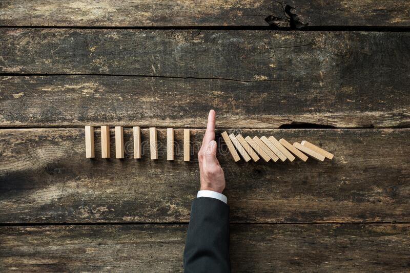 Conceptual image of stock market and business crisis. Aerial view of hand of a businessman stopping collapsing dominos in a conceptual image of stock market and stock image