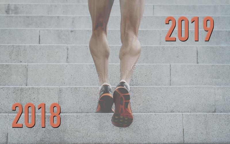 Reach your goals in 2019 conceptual image of Strong legs of young man running up city stairs stock images