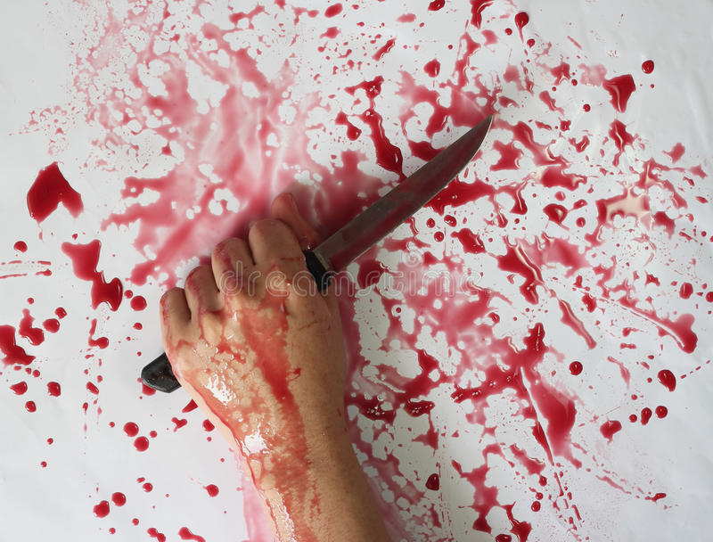 Conceptual image of a victim hand holding a sharp knife with blood on it resting on a concrete floor. Concept photo of murder and stock photography