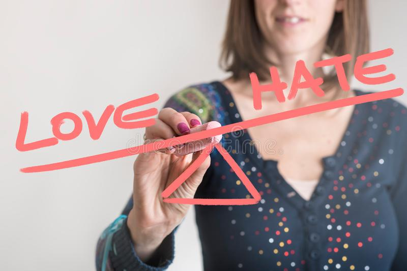 Word Love being weighted more than the word Hate. Conceptual image of a woman drawing a seesaw showing an imbalance between word Love being weighted more than royalty free stock photos