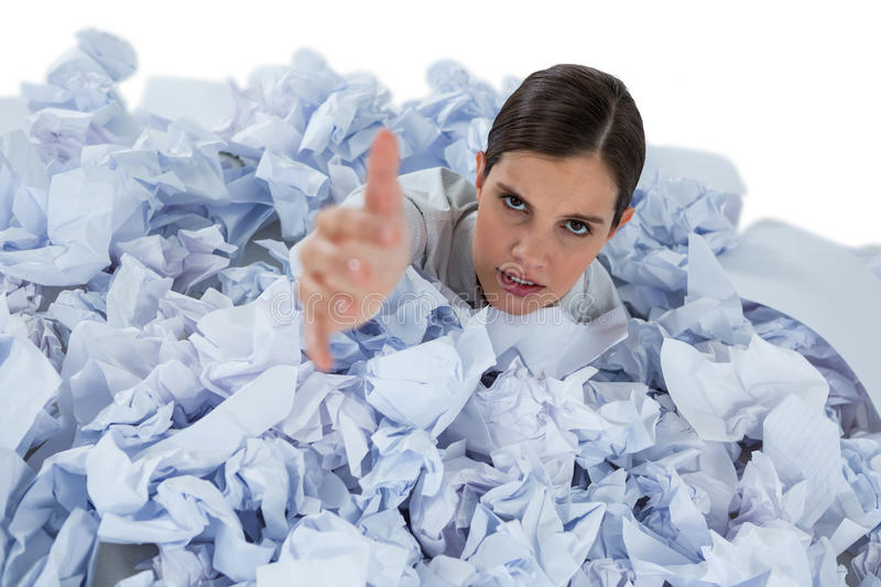 Conceptual image of woman in heap of crumple paper asking for help royalty free stock images