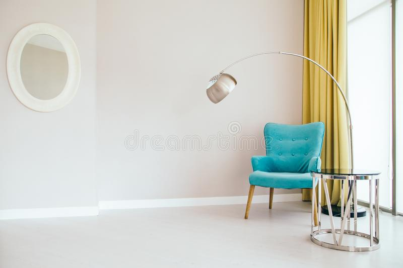 Interior of living room. Conceptual light  interior of living room with blue armchair, metallic standing lamp,  glass round coffee table , oval mirror, large royalty free stock photography