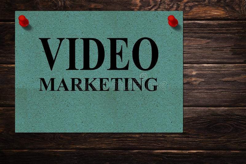 Conceptual messages `VIDEO MARKETING` written on green paper stands as an advertisement on a wooden surface. stock photos