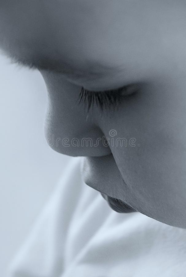 Monochrome old style photo of little boy who looking down. Conceptual Monochrome old style photo of little boy who looking down. Close up portrait royalty free stock image
