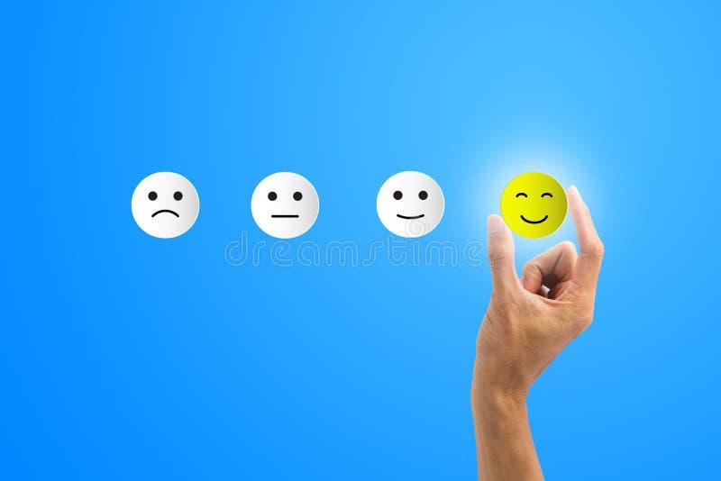 Conceptual o cliente respondeu ? avalia??o O cliente que usa a mão escolhe o ícone feliz do sorriso da cara no fundo azul descrev fotos de stock royalty free