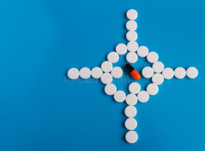 Conceptual para la producción farmacéutica Drogas redondas blancas de la píldora presentadas en un fondo azul bajo la forma de vi foto de archivo libre de regalías