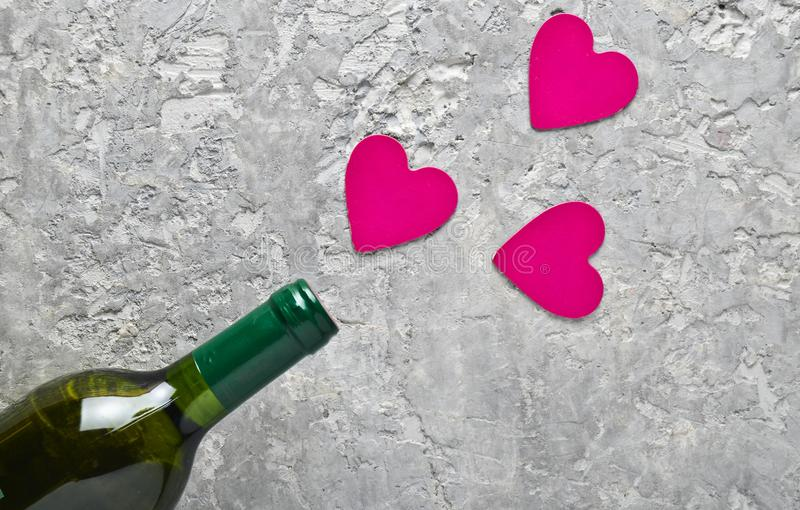 Conceptual photo Bottles of wine and pink decorative hearts. Love, romantic concept, top view. royalty free stock images
