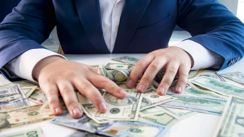 Conceptual photo of greed and avarice. Businessman grabbing money lying on office desk royalty free stock photography