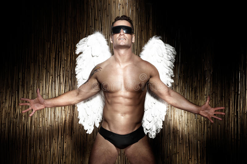 Conceptual photo of handsome, muscular male angel. royalty free stock image
