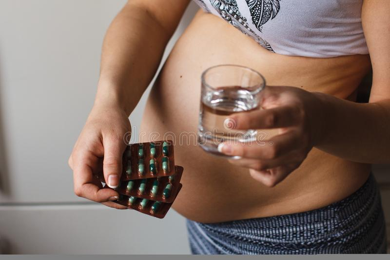 Conceptual photo of pregnancy bell and vitamin pills in blister pack royalty free stock images