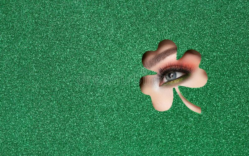 Conceptual photo of St. Patrick`s Day. The Eye of the Young Beautiful Woman with Bright Golden Shadows and Expressive Eyebrows, Looks in the Shamrock Leaves stock photography