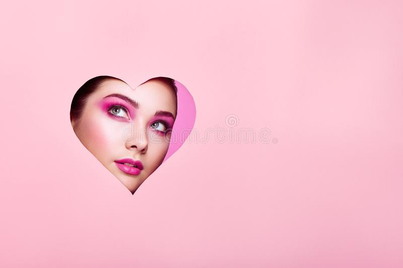 Conceptual photo of Valentine`s day. Face of Girl with Festive Pink Makeup. Paper hearts on a pink background. Love symbols Valentines day royalty free stock photography