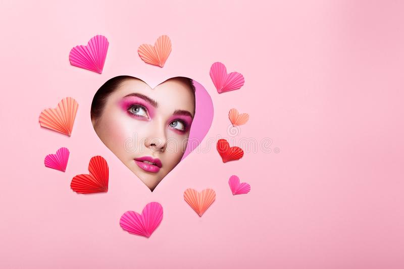 Conceptual photo of Valentine`s day. Face of Girl with Festive Pink Makeup. Paper hearts on a pink background. Love symbols Valentines day stock image