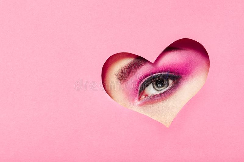 Conceptual photo of Valentine`s day. Eye of girl with festive pink makeup. Paper heart on a pink background. Love symbols Valentines day stock photography