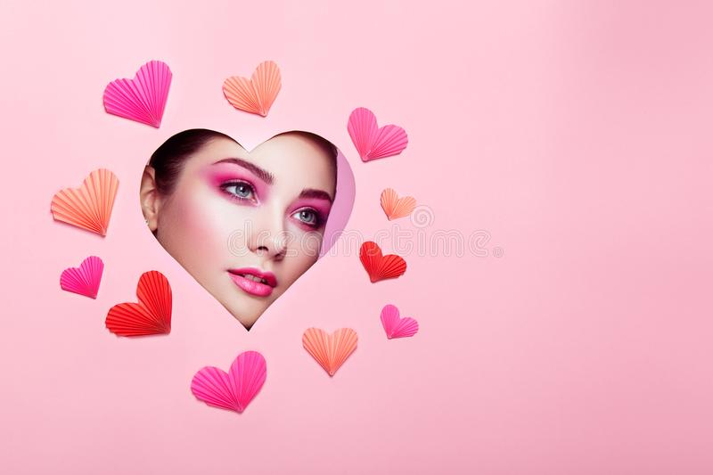 Conceptual photo of Valentine`s day. Face of Girl with Festive Pink Makeup. Paper hearts on a pink background. Love symbols Valentines day stock photos
