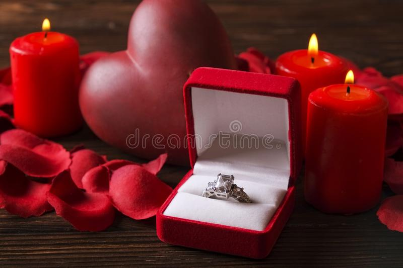 Conceptual photo of wedding or engagement ring with candles in shape of heart. St. Valentine`s day. Marry me concept, wedding / engagement ring with red candles royalty free stock photos
