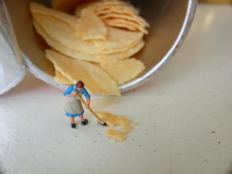 Conceptual, Photo 1 woman cleaning spill of cheese potato chips. Photo 1 woman cleaning spill of cheese potato chips stock photo