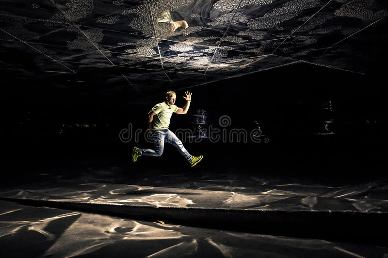 Conceptual photo of young and attractive man in jump on black background. stock photo