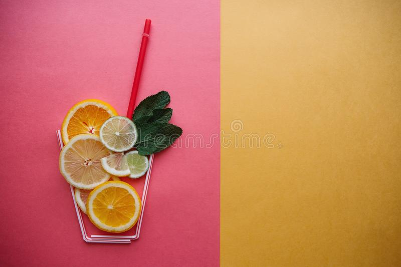 Conceptual photography. Citrus lemonade or juice from fresh fruits in a glass of tubules royalty free stock images