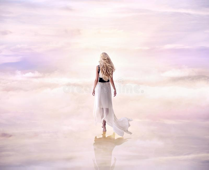 Conceptual picture of a blond lady walking on the delicate, fluffy clouds royalty free stock photography