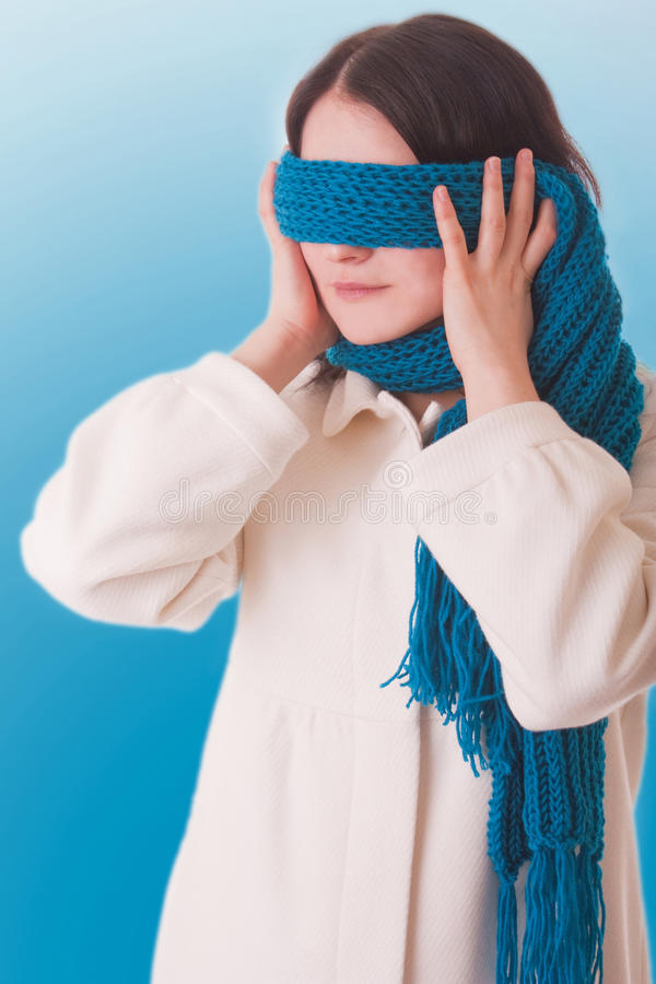 Conceptual picture. A girl tries to hide from the outside world, shutting his eyes with a scarf stock images