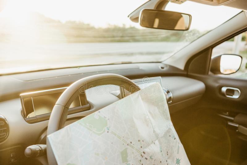 Conceptual picture of road travel or tourism or traveling by car. Map inside the car on a sunset background stock photography