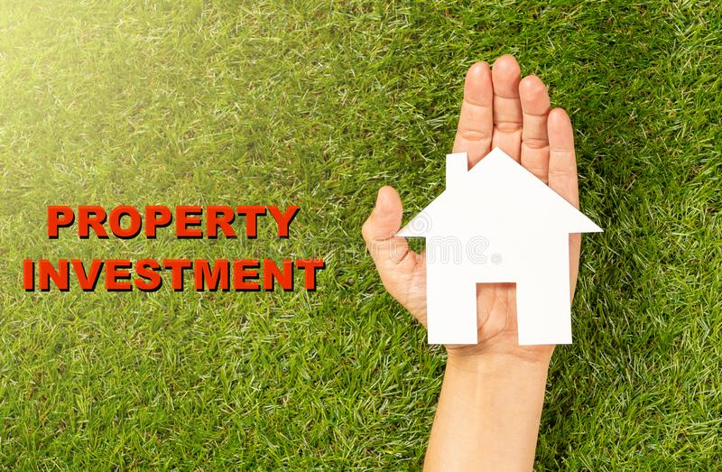 White house on woman hand and text Property Investment written on grass in Housing Market concept stock images