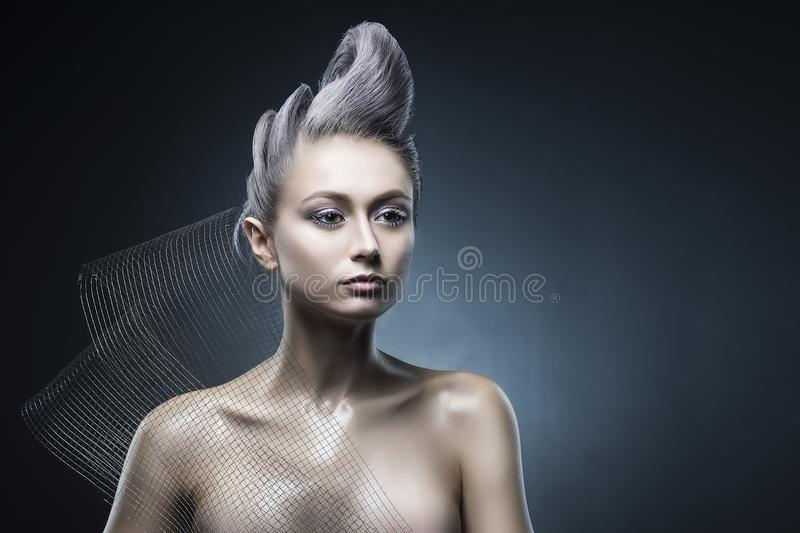 Conceptual portrait of beautiful naked shoulders vanguard hairstyle metallic colour hair girl wearing steel construction armature stock images