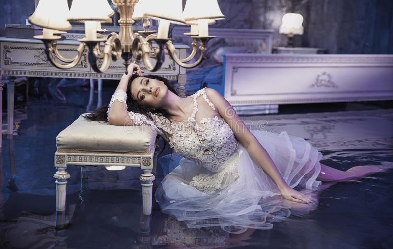 Conceptual portrait of an elegant woman in the flooded, antique stock image