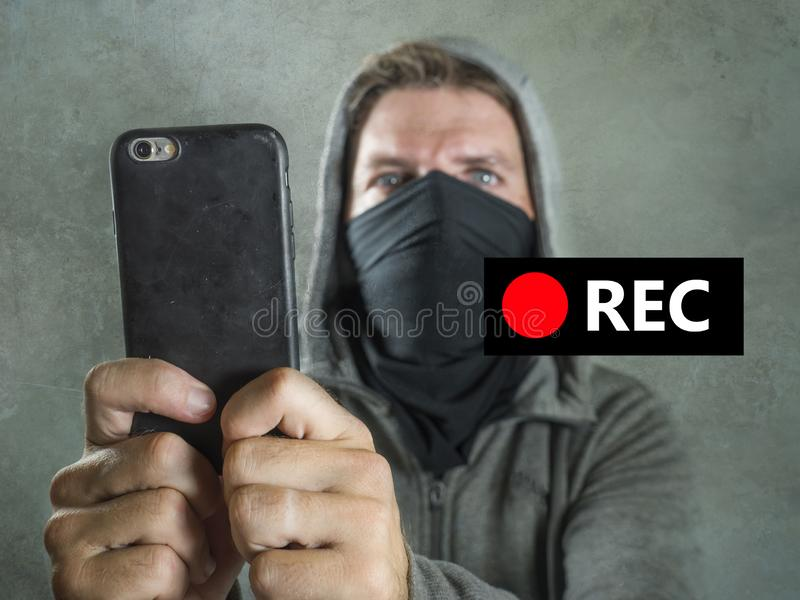 Conceptual portrait of young rioter filming street chaos . ultra and radical man masked recording riot video on mobile phone stock images