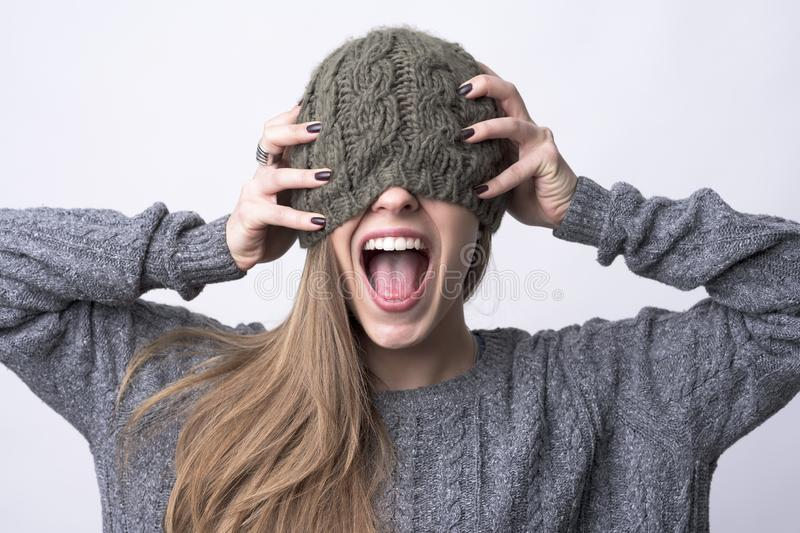 Conceptual portrait of young woman screaming with cap over her eyes and hands on head royalty free stock photography