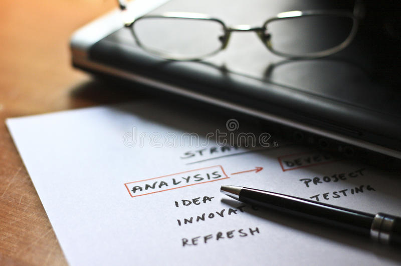 Conceptual scheme for a business strategy. Business strategy plan workflow diagram written on a paper with computer in the background. Conceptual scheme for stock photography