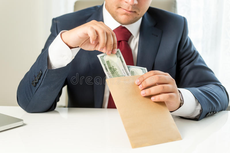 Conceptual shot of bribed politician taking envelope with money. Conceptual photo of bribed politician taking envelope with money royalty free stock images