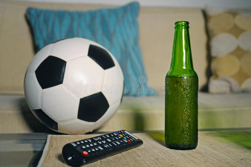 Conceptual watching football game at sofa on television with beer bottle and popcorn bowl in friends enjoying soccer game TV. Conceptual still life no people royalty free stock photos