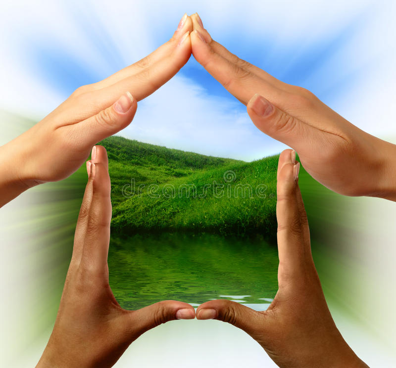Conceptual Symbol Home Made by Hands. Conceptual symbol home made by black and white people hands framing the nature scenery stock photography