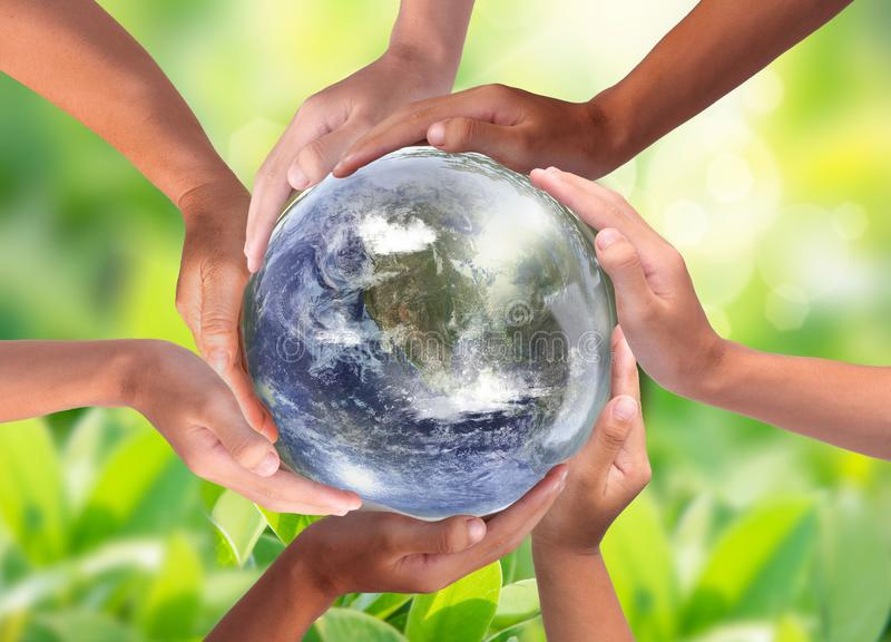 Conceptual symbol of multiracial human hands surrounding the Earth globe. Unity, world peace, humanity concept. World environment day stock photo