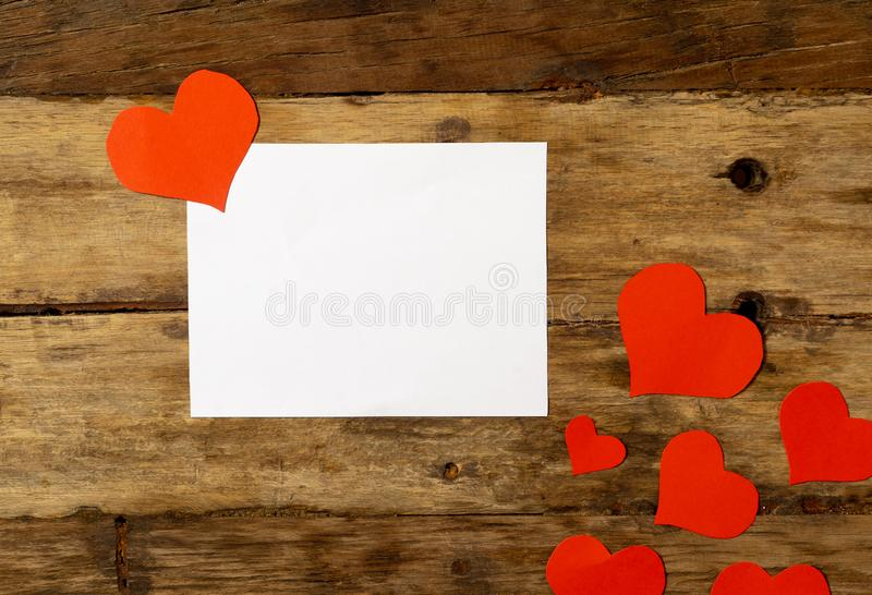 Conceptual Valentines image of white paper note with space for text and red hearts on wood table stock images