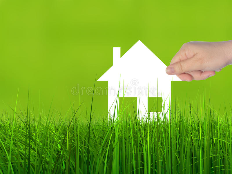 Conceptual white paper house symbol held in hand in green grass. Concept or conceptual white paper house symbol held in hand by a woman in green summer grass stock image