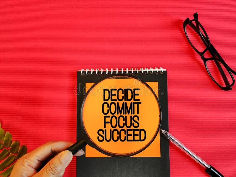 conceptual words of decide commit focus succeed on notepaper with glasses,pen and hand holding magnifier background royalty free stock images