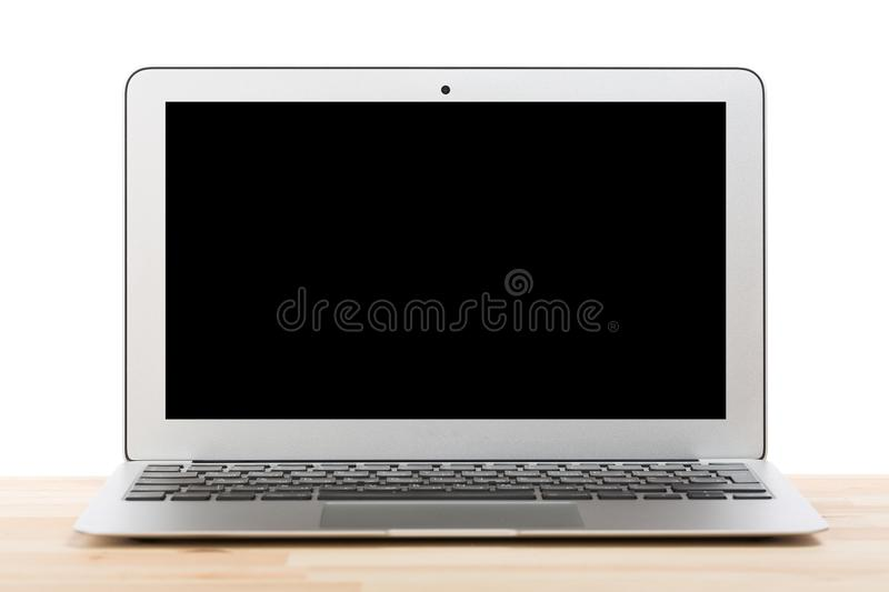 Conceptual workspace or business concept. Laptop computer with blank black screen on light wooden table. Isolated background. stock photo