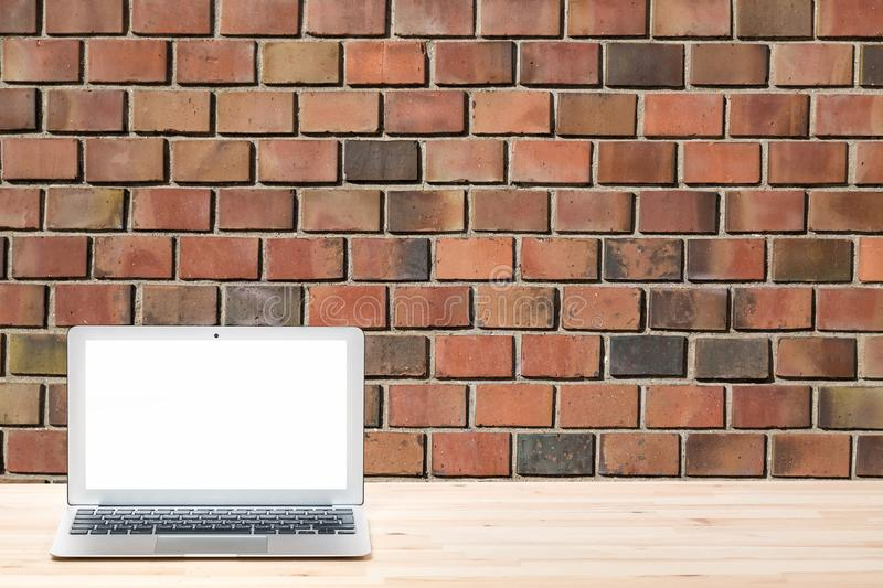 Conceptual workspace or business concept. Laptop computer with blank white screen on light wooden table against red brick wall or royalty free stock images