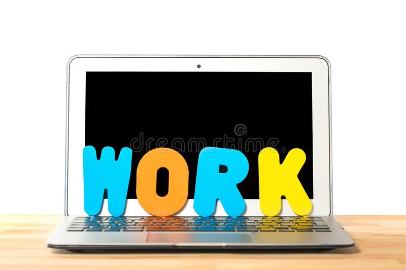 Conceptual workspace or business concept. Laptop computer with word WORK from colorful letters against isolated white background royalty free stock photo