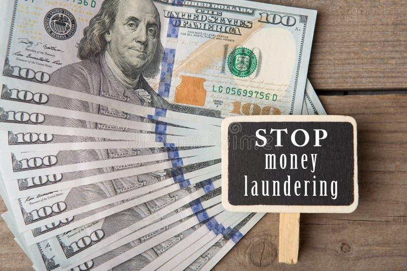 Conceptueel beeld met bord met tekst & x22; eindegeld laundering& x22; en honderd dollarsrekeningen stock foto